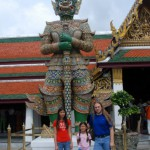 """Wat Prakaew is protected by statues of giants known as """"Yuk."""" I had to get this picture because somewhere in my parents home in Tampa there's a picture of my brother and I when I was nine and Anek was about 6 (close to Jeliya's current age), standing beneath a yuk at this same location."""